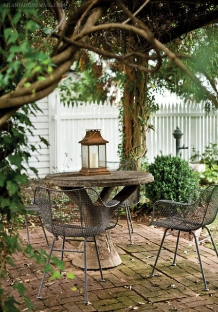 a mini rustic pergola all covered with plants, with a stone table and metal chairs