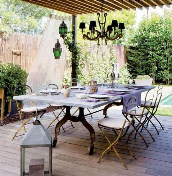 a vintage meets rustic patio with exquisite furniture, some lanterns and a chandelier plus curtains