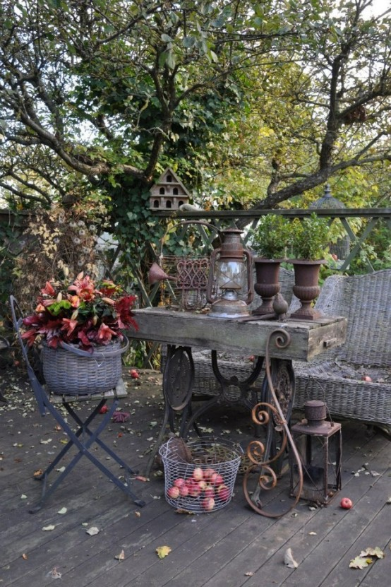 a vintage meets rustic patio with wicker furniture, a vintage stone and metal table, potted leaves