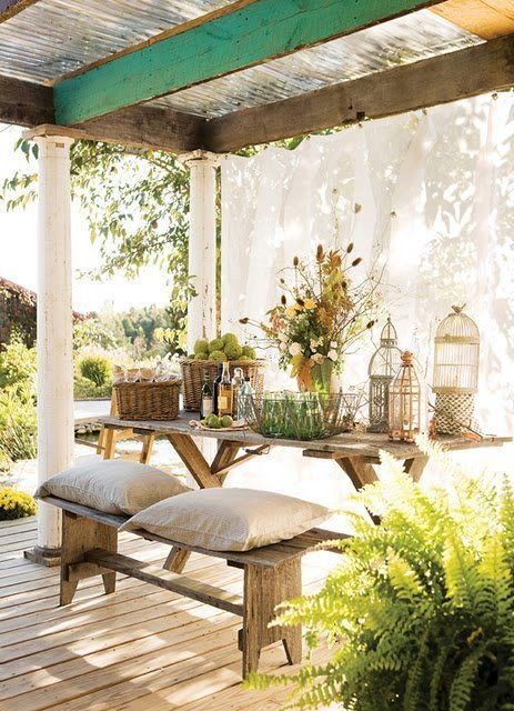a welcoming rustic patio with pillars, curtains, wooden furniture and potted greenery