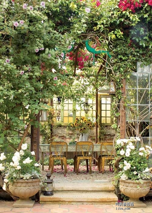 a rustic meets vintage patio with a shabby chic table and yellow chairs, potted greenery and blooms all over