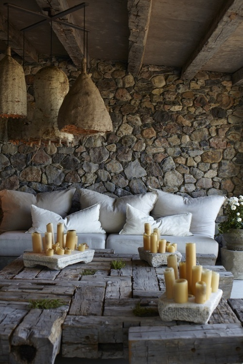 a rustic patio with stone walls, wicker lamps, a low rough wood table with lots of candles