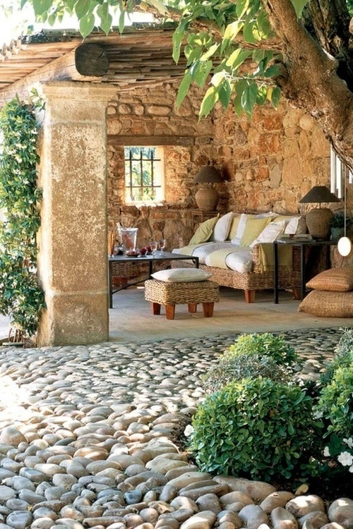 a rustic patio done with stone walls, wicker furniture, neutral textiles and lamps