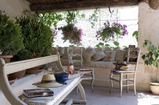 a neutral patio with stone walls, whitewashed wooden furniture, potted greenery and blooms