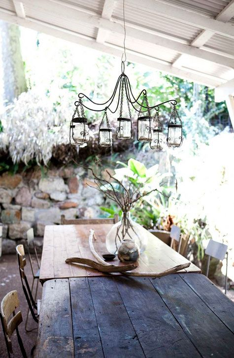 a rustic patio with stone walls, wooden furniture and candle lanterns hanging over the table