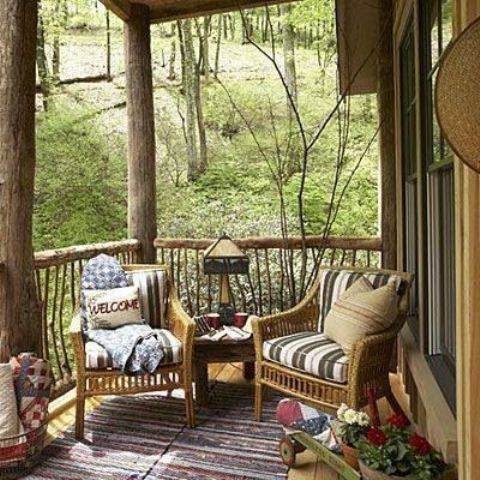 a small rustic patio with wicker furniture, potted blooms and colorul textiles