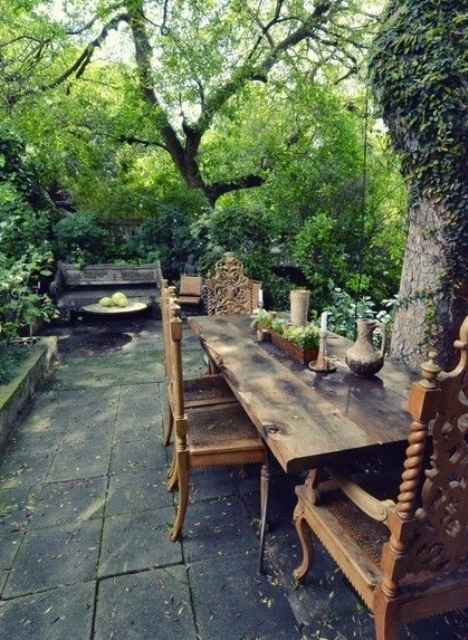 a rustic patio with a tile floor, a wooden bench and a wooden dining set plus much greenery