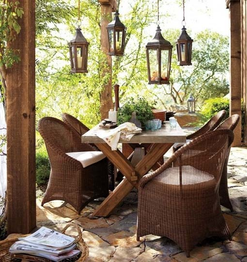 a cozy rustic patio with wicker chairs, a wooden table and wooden lanterns hanging over the table