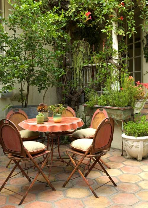 a rustic meets vintage patio with vintage wooden chairs and a table, potted greenery and blooms around