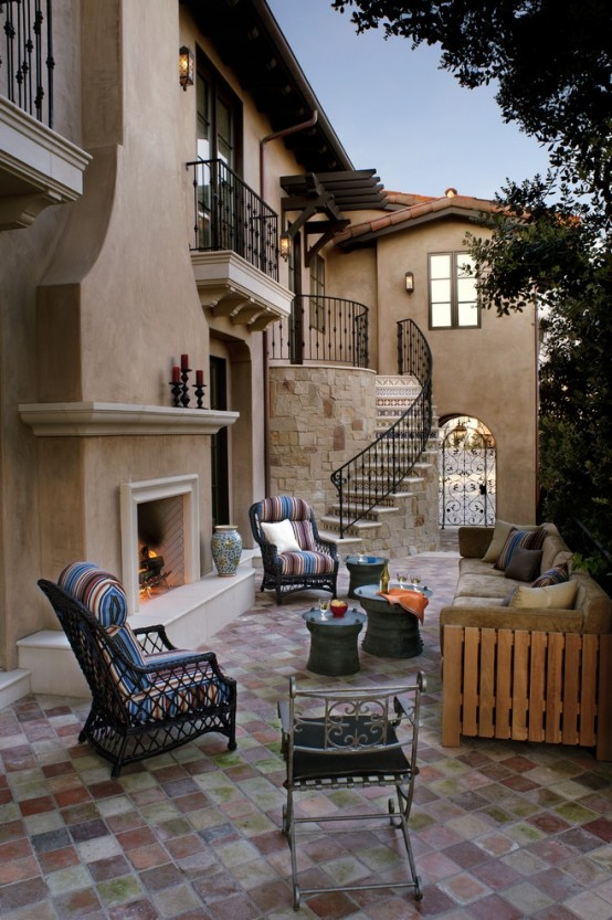 an elegant patio with a rustic feel, a neutral fireplace, wooden and wicker furniture and colorful textiles