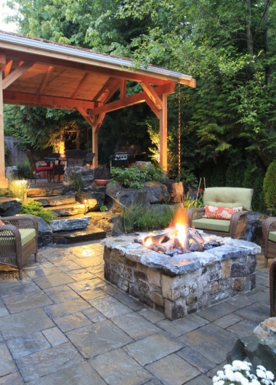 a rustic space done with tiles and stone, with a fire pit, comfy furniture and an outdoor kitchen
