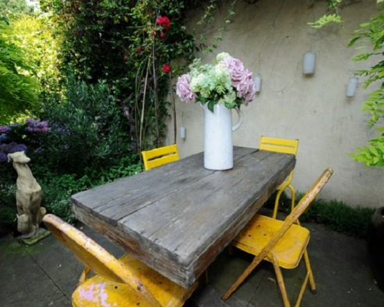 a cozy rustic patio with a wooden table, bold yellow chairs and potted blooms