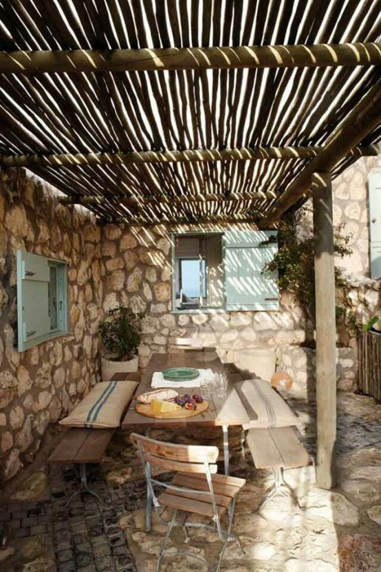a rustic space with stone walls, wooden furniture, potted greenery and striped pillows