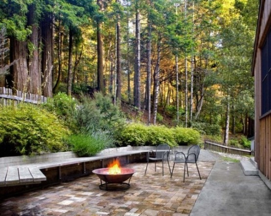 a contemporary meets rustic patio with a long wooden bench, a fire pit and a couple of chairs