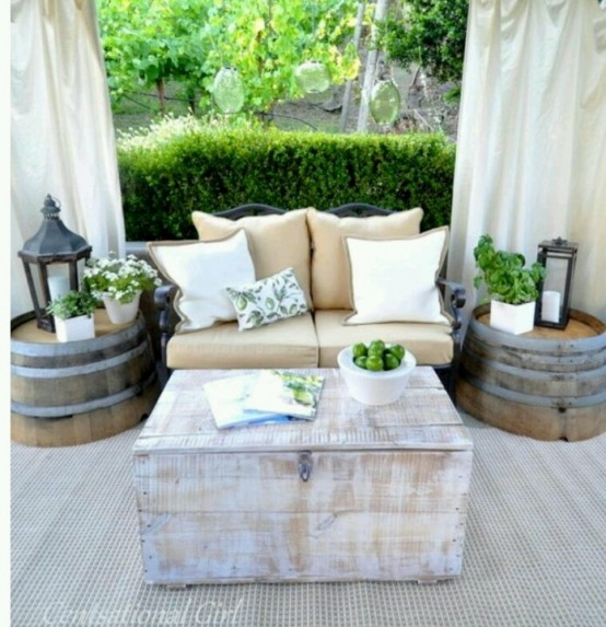 a bright rustic patio with barrels as side tables, a wooden chest, a comfy sofa and curtains for privacy