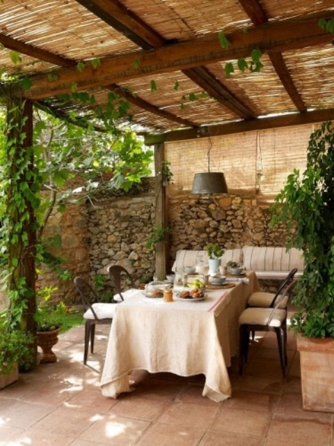 a welcoming patio with stone walls, wooden furniture, potted greenery and wicker lampshades