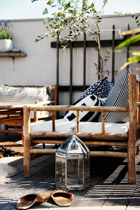 a cozy Scandinavian meets rustic patio with rattan furniture, black and white textiles and metal lanterns