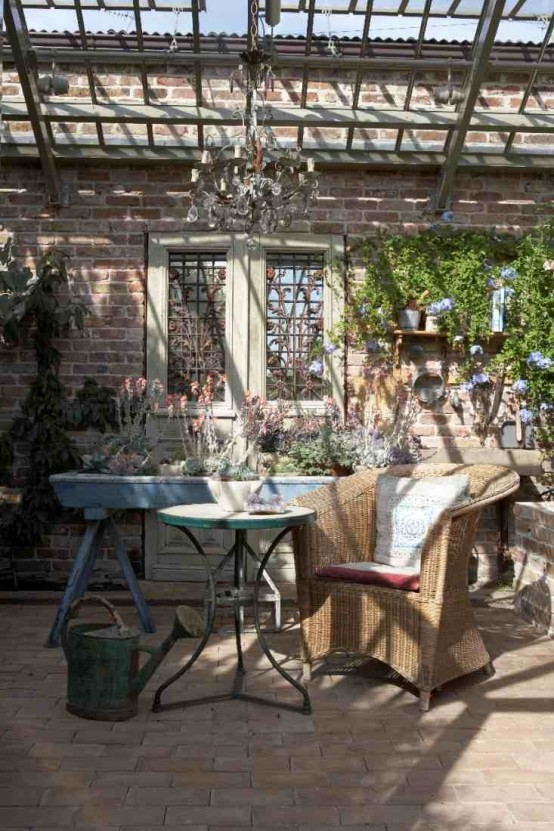 a rustic meets vintage patio with vintage and wicker furniture, with a crystal chandelier and potted blooms