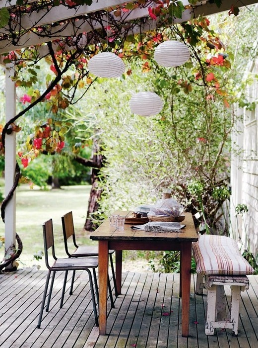 a rustic vintage patio with wooden and metal furniture, lanterns and lots of greenery