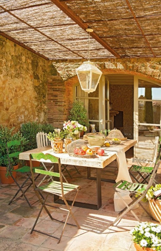 a French countryside patio with stone walls, wooden and metal furniture and a pendant lamp