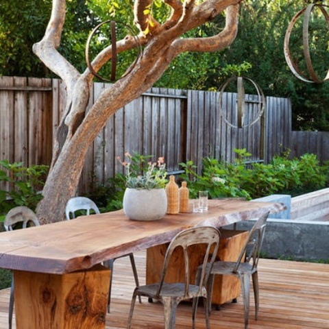 a rustic meets conemporary patio with a living edge table, metal chairs and metal sphere lamps
