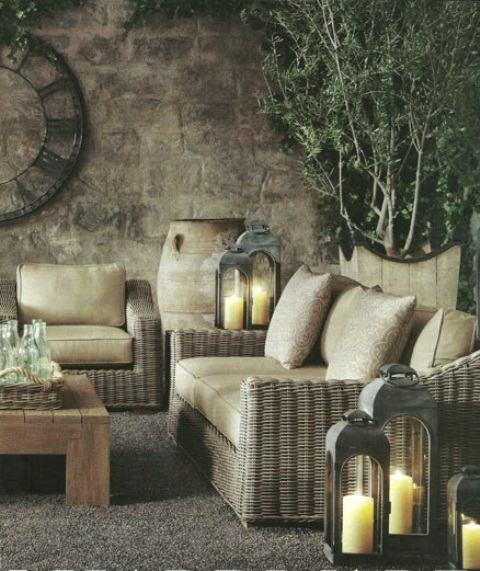 a Mediterranean rustic patio with wicker furniture, potted greenery, candle lanterns and a vintage clock