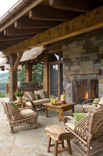 a rustic patio with rattan and wooden furniture, with a stone fireplace and touches of bright green