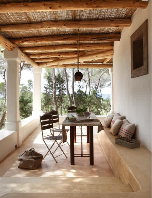 a neutral rustic patio with wooden furniture, a concrete bench going along the patio and pendant lanterns