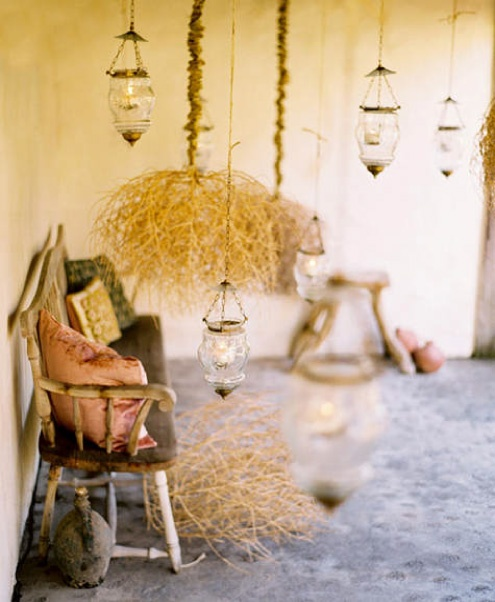 a vintage meets rustic patio with a wooden bench, some hay and pendant lamps