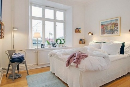 a welcoming Scandinavian bedroom with a white bed, a metal chair, a rug and an artwork