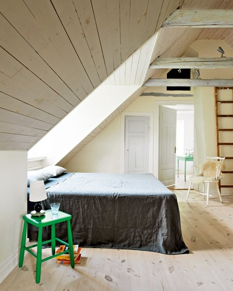 a laconic attic Nordic bedroom with a skylight, wooden covered walls and floor, some vintage furniture