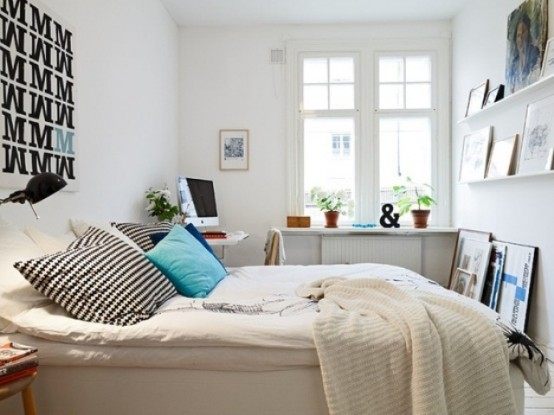 a small Scandinavian bedroom with a white bed, open shelves for storage, a desk in the corner and some graphics