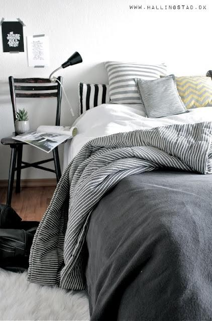 a chic Nordic bedroom with a black bed, striped bedding, a black chair, a catchy lamp