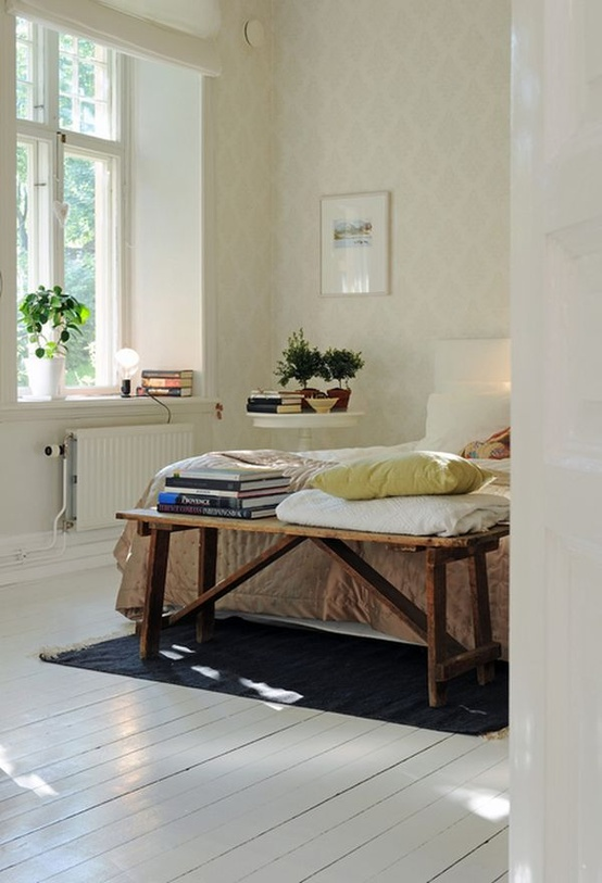 a cozy Scandi bedroom with printed wallpaper, a white wooden floor, a white bed and a rough wooden bench at the foot