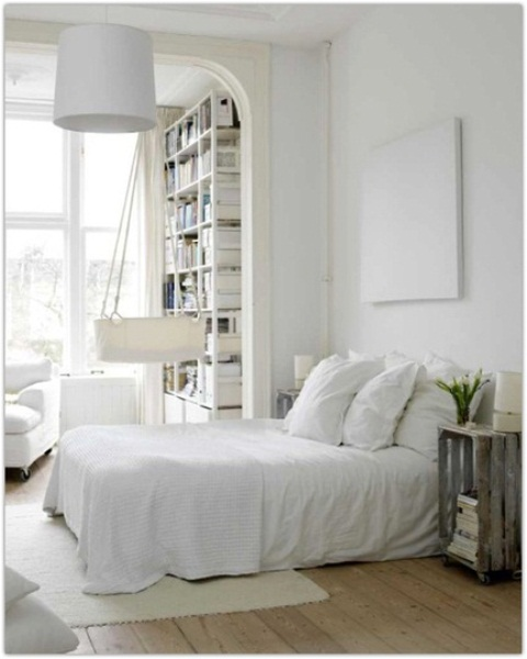 an airy Nordic bedroom with white furniture and bedding, an artwork, a pendant lamp and a crib hanging next to the bed