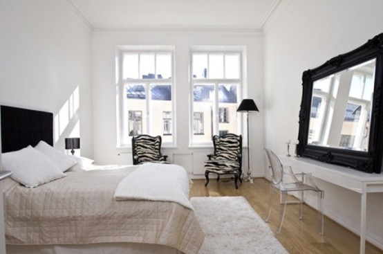 an airy Scandi bedroom with a blakc bed, mirror, chairs with a zebra print and a floor lamp