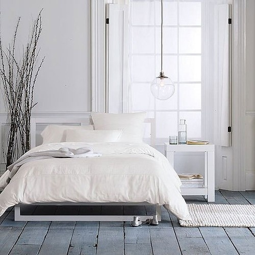 a simple Nordic bedroom with a whitewashed wooden floor, a pendant lamp, modern white furniture and a branch arrangement