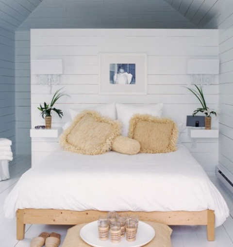 a Noridc meets coastal bedroom done in white and blues, wiht a wooden bed and wicker touches plus potted greenery