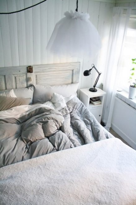an air-filled Scandinavian bedroom with white walls, a whitewashed wooden bed, white nightstands and pendant lamps