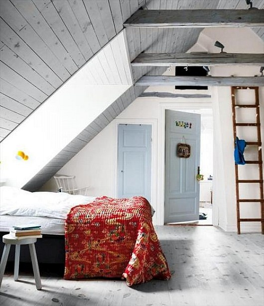 an attic Nordic bedroom with wooden planks on the ceiling, a skylight, vintage furniture and a ladder
