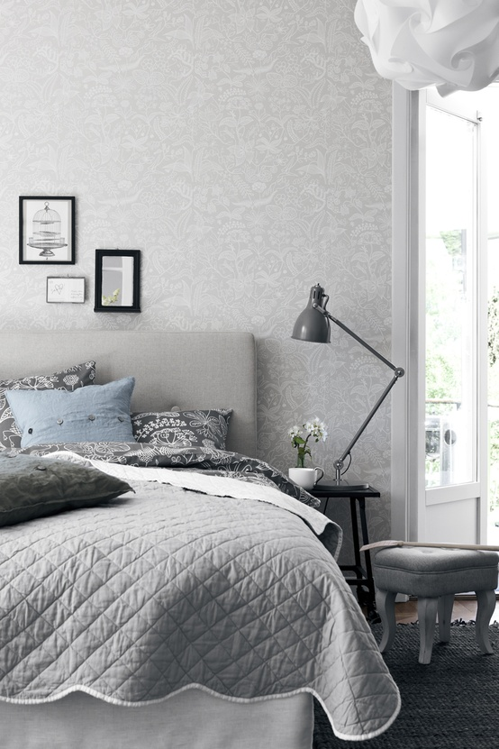a Nordic bedroom done in grey, with printed wallpaper, an upholstered grey bed, printed bedding and a nightstand