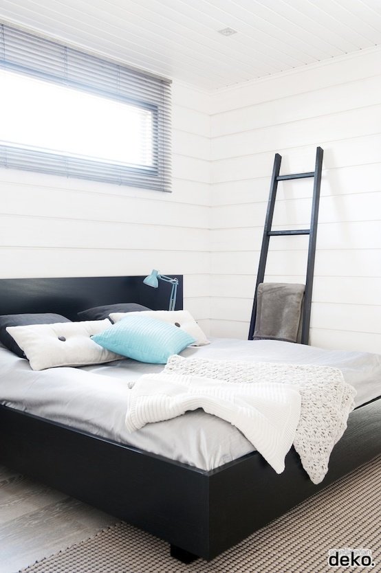 a peaceful bedroom done with white shiplap, a black bed for a contrast, a black ladder and touches of light blue