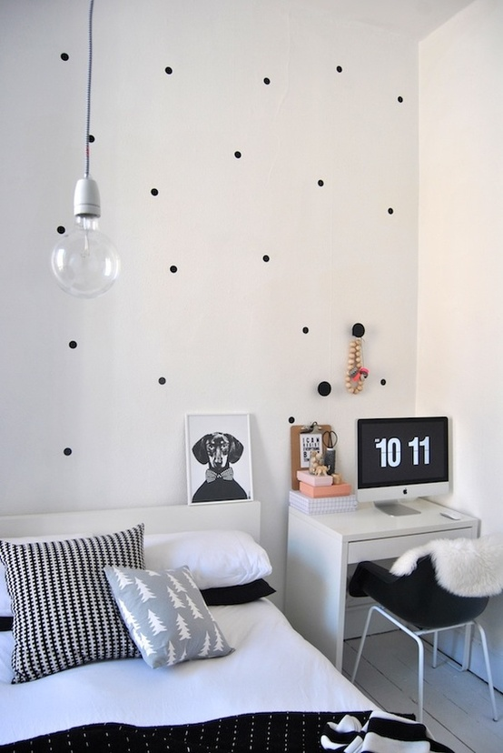 a monochromatic Nordic bedroom done with some prints, a bed, a deks space and a hanging bulb