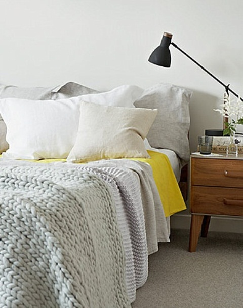 a Nordic bedroom with neutral bedding, a wooden nightstand, a black lamp
