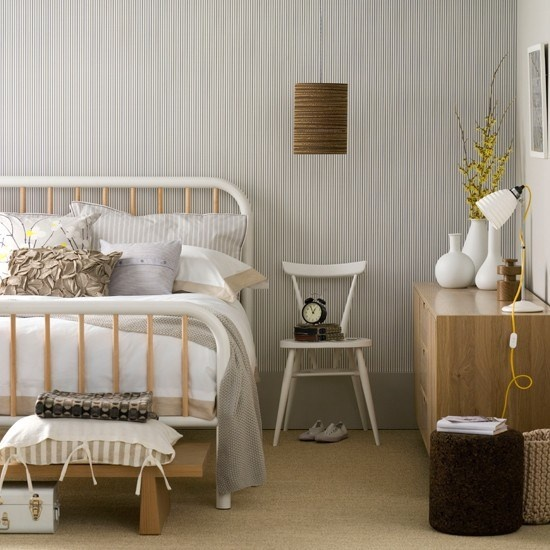 a Nordic bedroom with printed wallpaper, retro furniture, lamps, benches and a stool