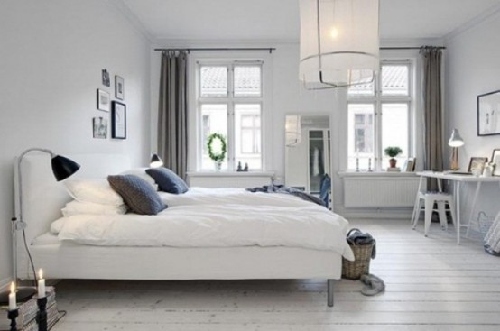 an airy monochromatic bedroom with a pendant lamp, a white upholstered bed, neutral bedding and lamps and lights