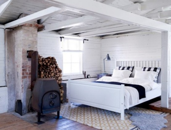 a vintage-inspired Nordic bedroom in white, with white planks, a metal hearth and a comfy bed plus rugs