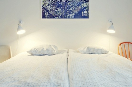 a Nordic bedroom with chairs and beds, wall lamps and a bright artwork