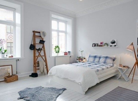 an airy Scandinavian bedroom with white walls and a floor, vintage rustic furniture and lamps and greenery