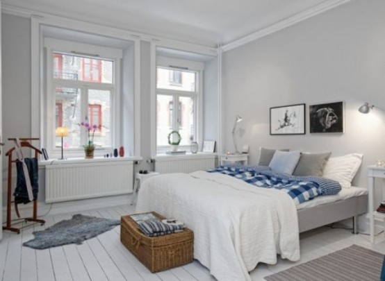 an airy Nordic bedroom with a grey bed, a basket for storage and some retro furniture